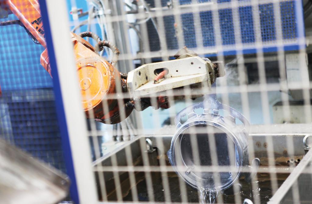 Робот-съемщик достает только что отлитый корпус из ванны охлаждения